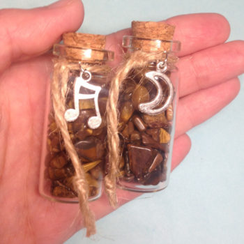 A glass jar with a cork, containing Tiger's Eye crystal chips, with a charm on twine around the top of the bottle