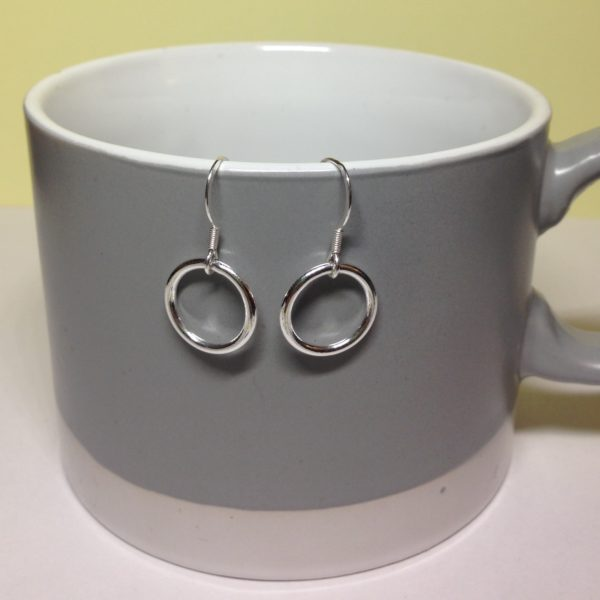 Circle of Karma Drop Chain Earrings on a mug to show their size