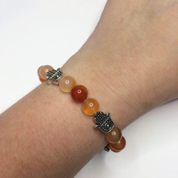 A Carnelian gemstone bead bracelet with five silver Hand of Fatima beads being worn on a woman's wrist