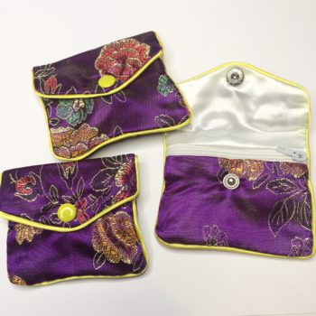 The front of three unique purple Floral Crystal Pouch