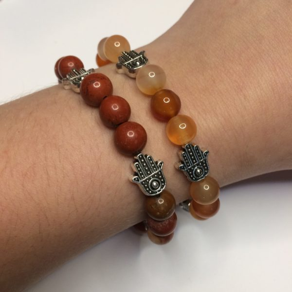 A Red Jasper and an orange carnelian gemstone bead bracelets with five silver Hand of Fatima beads being worn on a woman's wrist